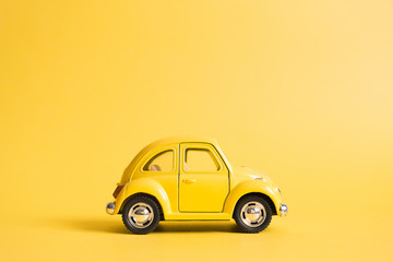 Omsk, Russia - May 26, 2019: Yellow retro toy car on yellow background. Valentines day. Womens Day. Summer travel concept. Taxi