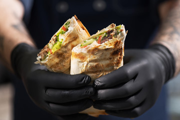 Burrito, lamb shawarma - the best street food. Close-up of men's hands chefs with shawarma.