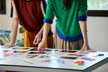 Colleagues Choosing Photographs At Desk In Office
