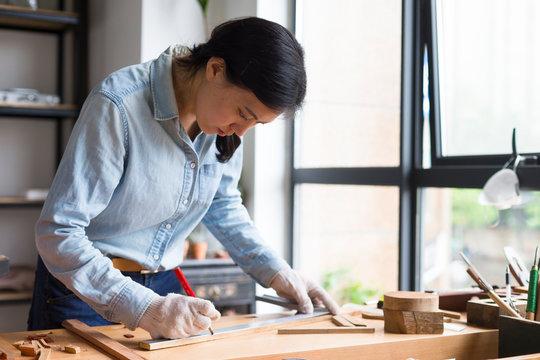 Female carpenter working In Carpentry Workshop
