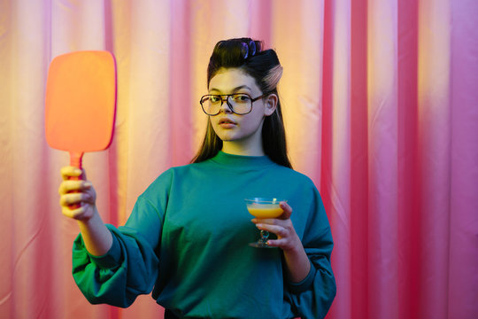 Portrait of young woman holding cocktail glass and mirror