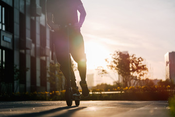 Close up of man riding black electric kick scooter at cityscape at sunset