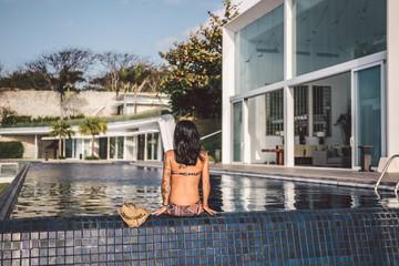 beautiful tattoed woman sitting at a pool beside a luxury villa