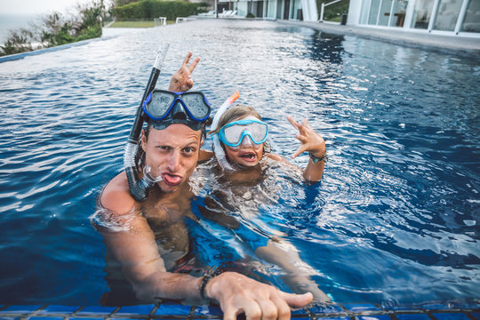 father and son with snorkeling gear having fun in a huge pool