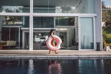 beautiful woman with inflatable pink donut in front of luxury property