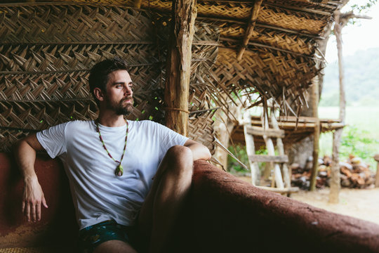 Handsome Man Sitting In A Tropical Hut