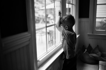 Moody black and white images of a bored young boy looking out a window