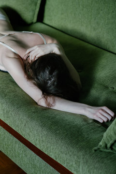 Close up of anonymous skinny female model in underwear sitting on the sofa from back