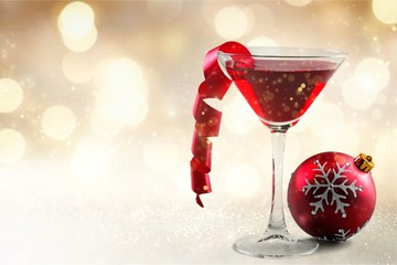 Glass of red wine and Christmas decoration on background
