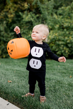 toddler dressed in a homemade electrical outlet costume for Halloween holds his jack-o-lantern for collecting candy
