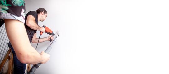 Handwerker bohrt Loch in die Wand mit einer Schlagbohrmaschine in einer Wohnung