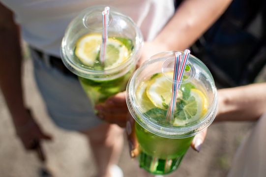 girls holding mojito in plastic glasses, close-up of refreshing cocktails