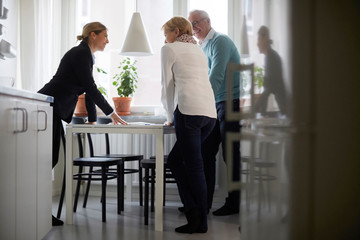 Smiling estate agent and senior couple discussing over documents of new house