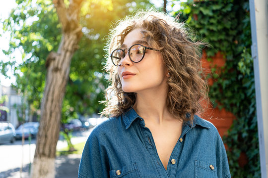 Outdoor close up portrait of young beautiful stylish happy smiling curly girl wearing sunglasses, posing in street. Sunny day light. Summer fashion concept. Copy, empty space for text