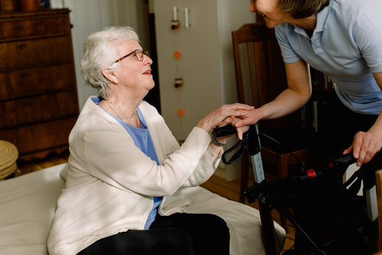Senior woman holding hand of healthcare worker while talking in nursing home