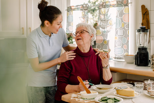 Senior woman having breakfast while talking with healthcare worker