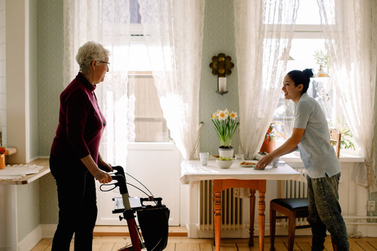 Smiling young female caregiver serving breakfast while looking at retired senior woman walking with rollator in nursing