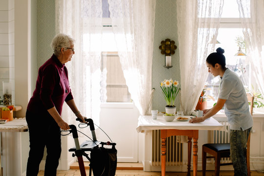 Retired senior woman walking with rollator while young female caregiver serving breakfast on table in nursing home