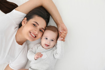 Portrait of mother with her cute baby lying on bed, top view. Space for text Fototapete