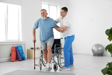 Professional physiotherapist working with senior patient in rehabilitation center