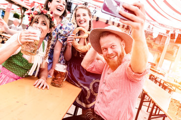 Fototapete - Gruppe von Freunden machen Selfies auf dem Oktoberfest im Bierzelt mit Bier beim Feiern