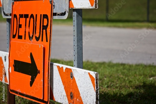 Detour sign pointing right on orange and white striped road