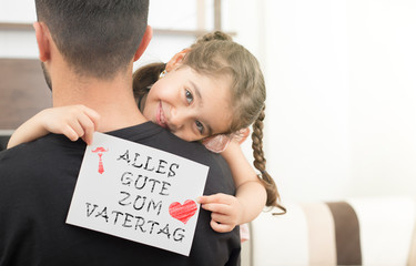 german lettering, fathers day happy birthday message.little girl hugging her father and showing the message of congratulation