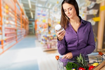 Woman with cart shopping and holding buttle in supermarket