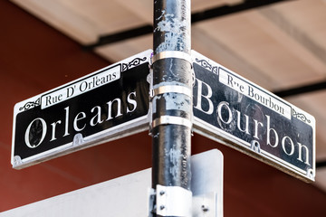 Orleans and Bourbon intersection Streets Sign text in New Orleans on lamp pole post isolated closeup