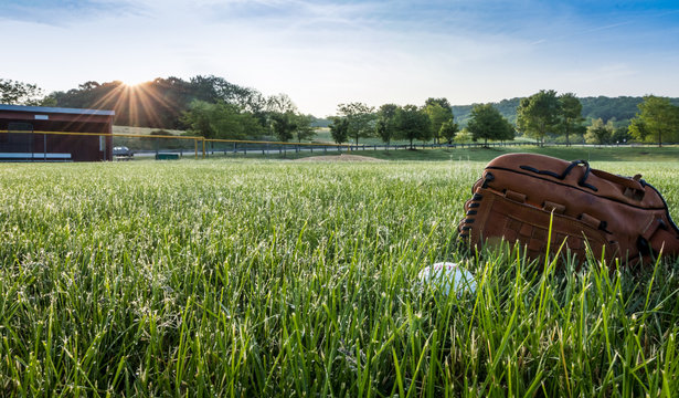 Baseball and glove in morning dew green grass