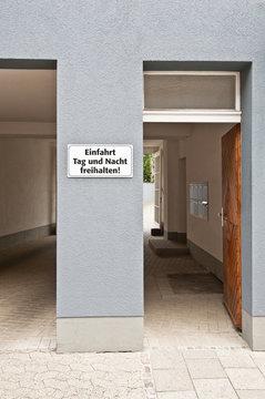 Weisses Schild - Einfahrt freihalten - auf einer Hauswand zwischen Toreinfahrt und Haustür