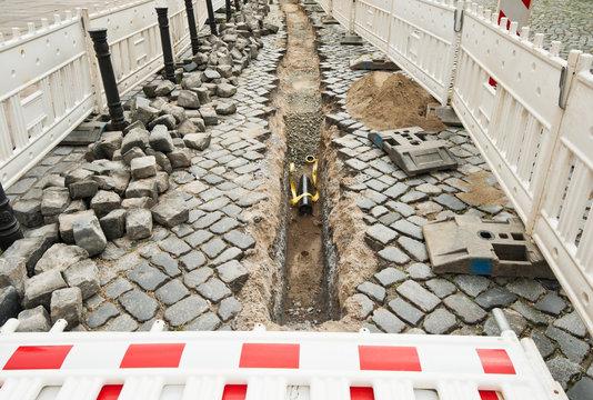 Einbau von Leerrohr in einer Strasse aus grossen alten Pflastersteinen