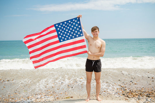 Caucasian male on a beach holding an American flag