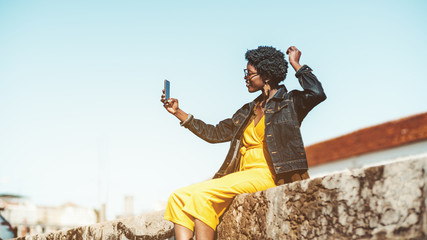 Dazzling black girl with curly Afro hair is taking a selfie on the smartphone outdoors while sitting on the top of a stone wall; a young charming African female is using her cellphone on the street Wall mural