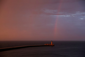 A yacht sails past the breakwater and lighthouse at the entrance to Grand Harbour as a rainbow is seen after heavy rainfall at sunset in Valletta