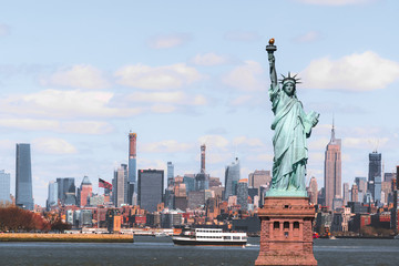 Fotomurales - The Statue of Liberty over the Scene of New york cityscape river side which location is lower manhattan,Architecture and building with tourist concept