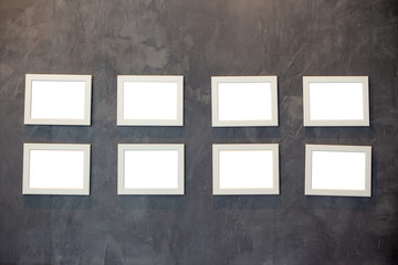 Collection of picture frames for paintings or photographs on the wall. Picture frames on Cement wall.