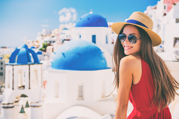Fototapete - Travel Europe summer holiday girl enjoying Oia, Santorini Greece cruise vacation. Sun getaway Asian woman smiling in hat and sunglasses.