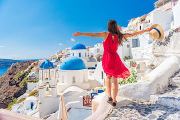 Wall Mural - Europe travel vacation fun summer woman dancing in freedom with arms up happy in Oia, Santorini, Greece island. Carefree girl tourist in European destination wearing red fashion dress.