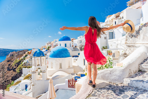 Wall mural Europe travel vacation fun summer woman dancing in freedom with arms up happy in Oia, Santorini, Greece island. Carefree girl tourist in European destination wearing red fashion dress.