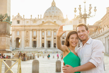 Rome selfie tourists couple by Vatican city and St. Peter's Basilica church taking photo with phone. Happy travel woman and man holding cellphone on romantic honeymoon in Italy.