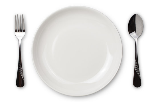 Dinner place setting. A white plate with silver fork and spoon isolated on white background. View from above.