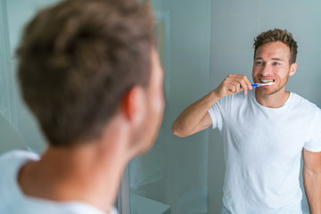 Brushing teeth man looking in mirror of home bathroom using toothbrush in morning routine for clean dental oral care.