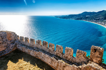 The fortress wall on the background of bright blue sea on a sunny day. Fototapete
