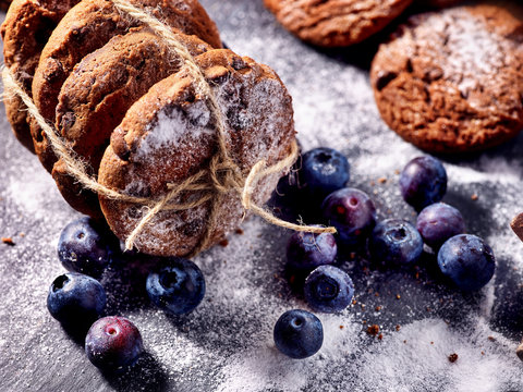 Serving food on slate onto wooden table. Oatmeal cookies biscuit with blueberry on picnic dark tiles countrylike. Chocolate Xmas holiday chip cookies tied with string. How and from what make sweets.