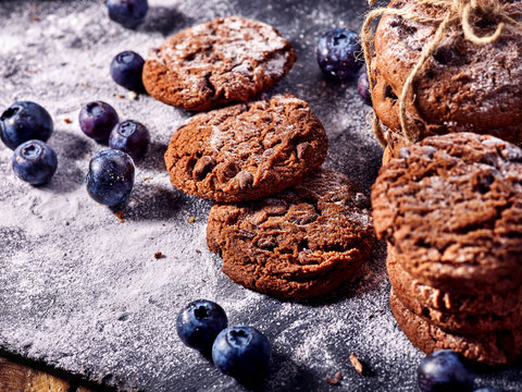 Serving food on slate onto wooden table. Oatmeal cookies biscuit with blueberry on picnic. Chocolate Xmas holiday chip cookies tied with string. Perfect product. Composition of confectionery.