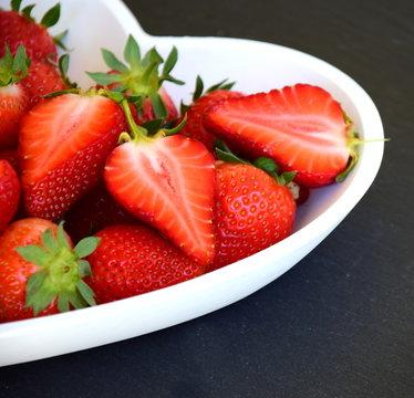 Rote reife Erdbeeren in einer weißen Herzschale auf dunkler Schiefertafel