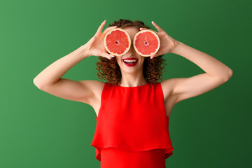 Happy young woman with tasty grapefruit on color background Fototapete