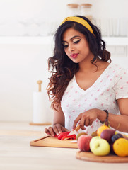 beautiful young indian woman cutting vegetables on the kitchen, healthy eating
