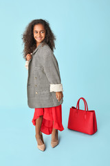 Stylish African-American girl in oversize clothes on color background